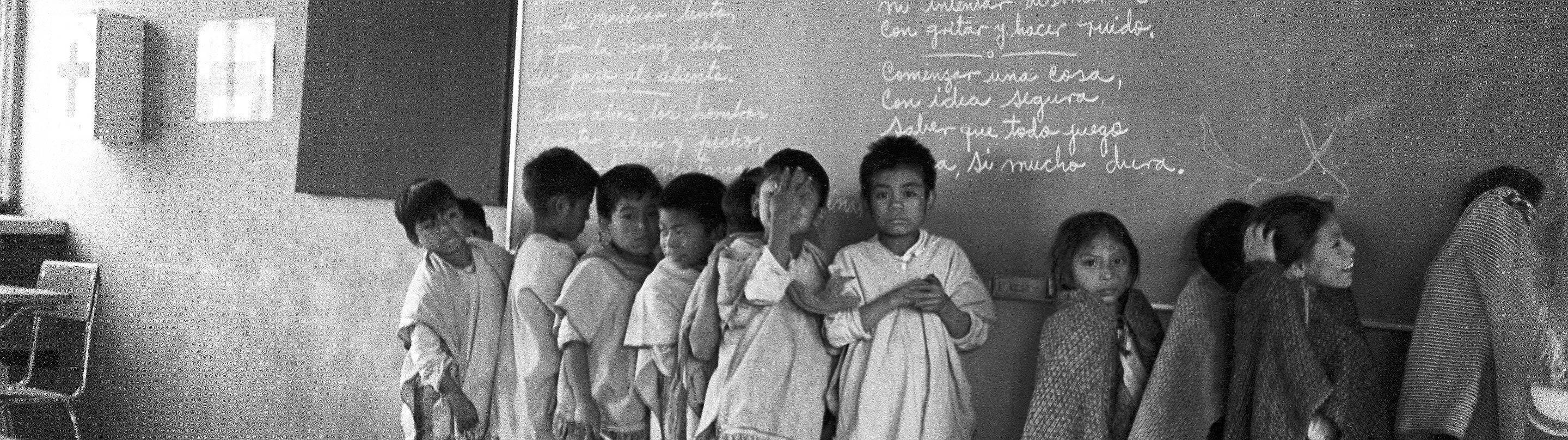 Detail of a black and white photograph of Maya children lined up by a blackboard